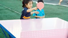 Small girl plays ping pong outdoors on a pink and blue table.
