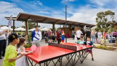 children playing a game of table tennis on the POPP ICON outdoor ping pong table in a reserve in Australia. Parents watch the game on the red and black table