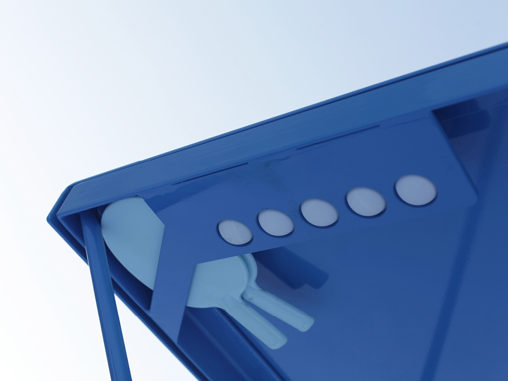 Close up of discreet table tennis equipment holder on the steel POPP ICON ping pong table. Blue outdoor ping pong table with blue racquets.