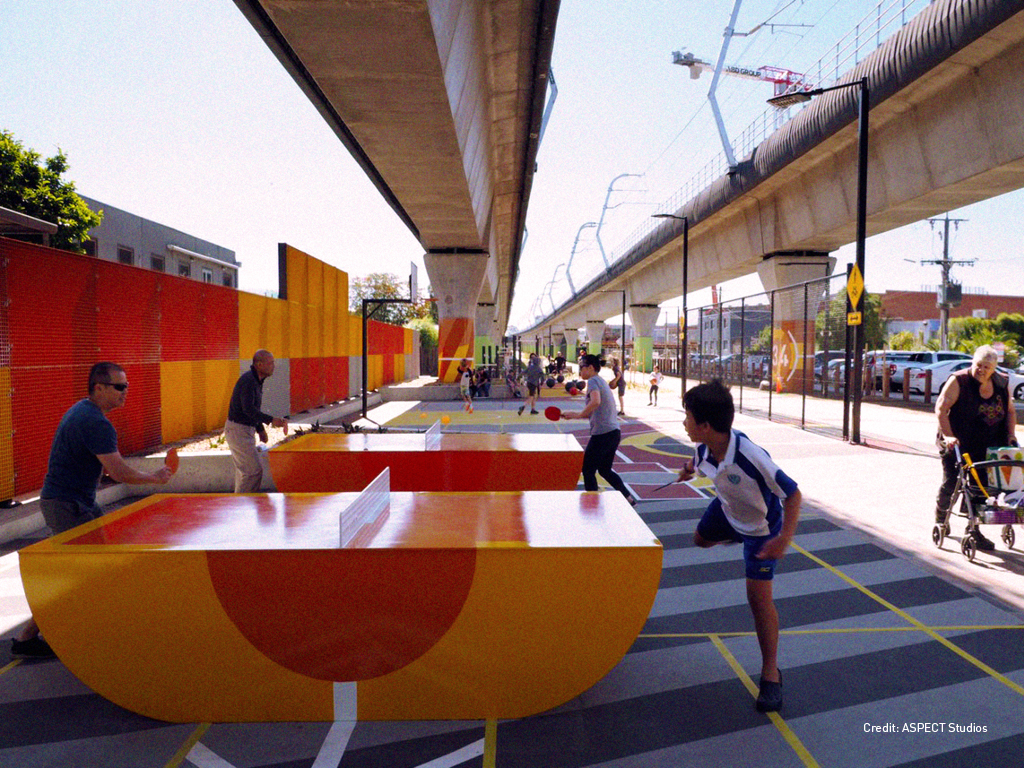 people playing ping pong on orange outdoor table tennis tables under a railway line in Melbourne Australia , a lady walks past on a walking frame watching the child playing.