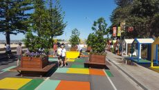 Yellow outdoor ping pong table on the esplanade in Altona Melbourne. People play a game of table tennis on the table