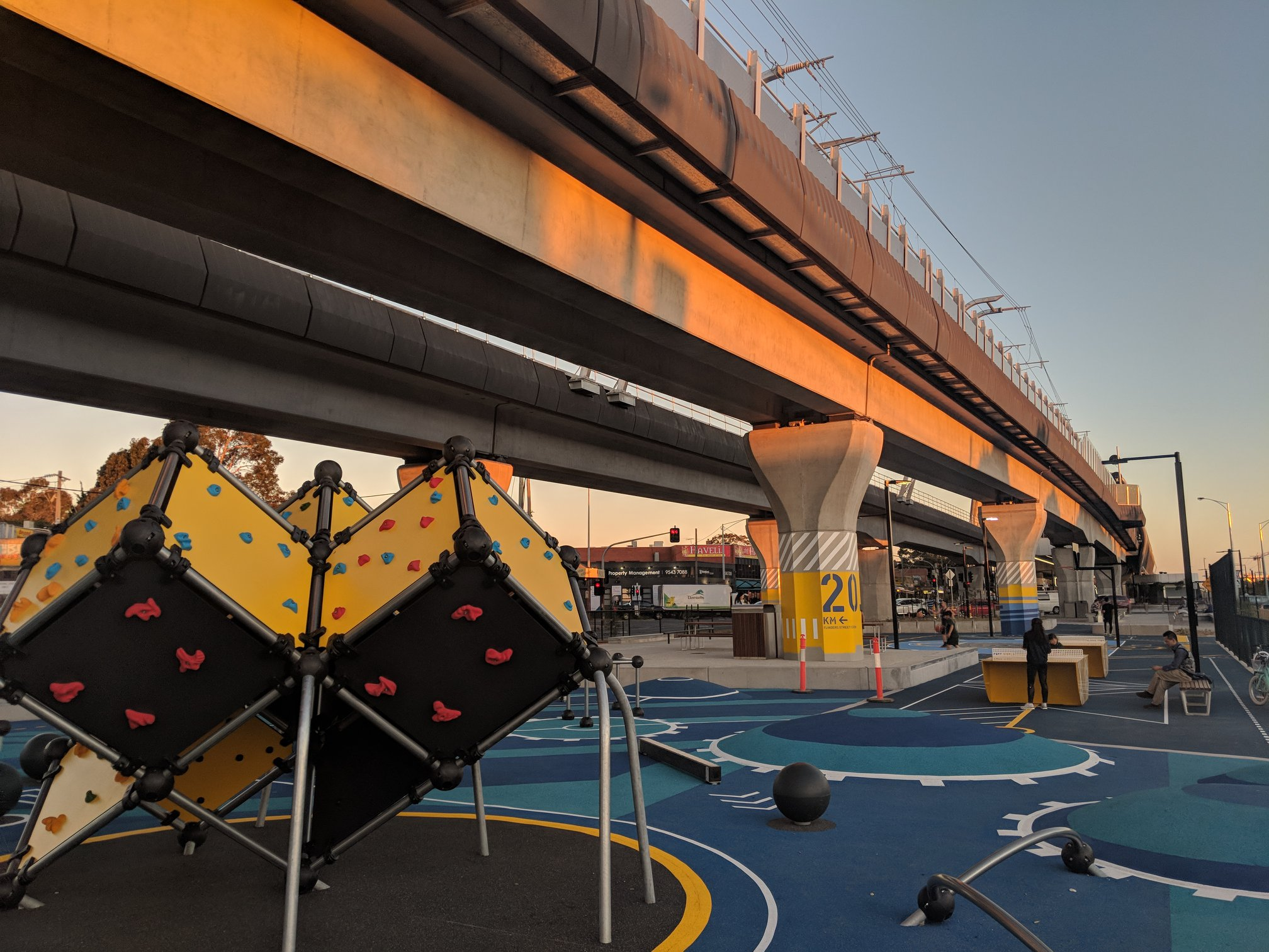 Under a railway line in Melbourne a game of table tennis is being played on two yellow steel ping pong tables, next to a rock climbing wall and fitness equipment.