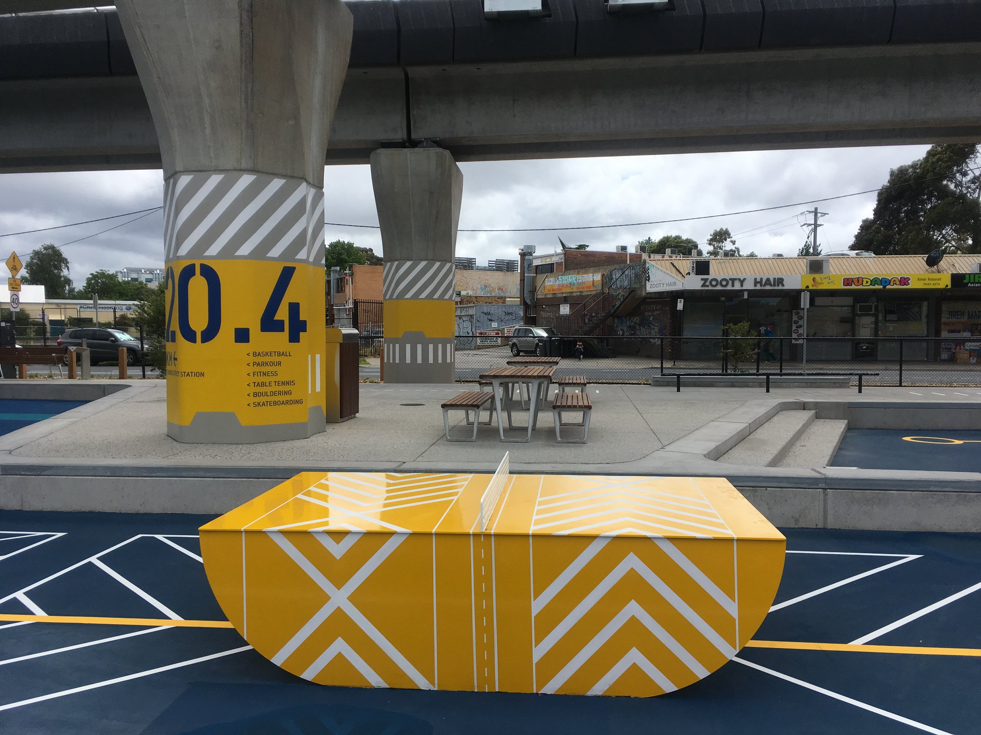 A yellow outdoor ping pong table is painted to match the surroundings, with geometric white lines. The ping pong table sits underneath a raised railway line in Melbourne, Australia.