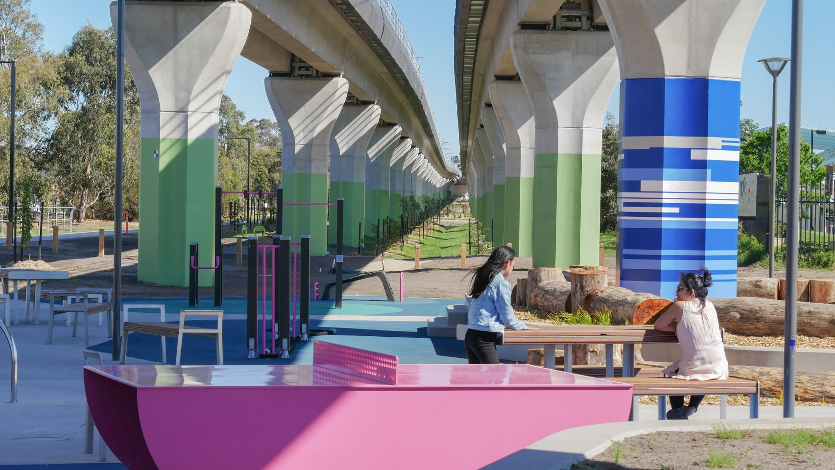 A pink HERO outdoor ping pong table sits under a raised railway line next to fitness equipment and a park bench. A mother and daughter sit on the bench in the new park space that has a blue and pink theme.