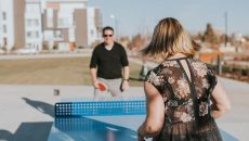A woman and a man are playing a game of table tennis on the ICON outdoor ping pong table in Calgary, Canada