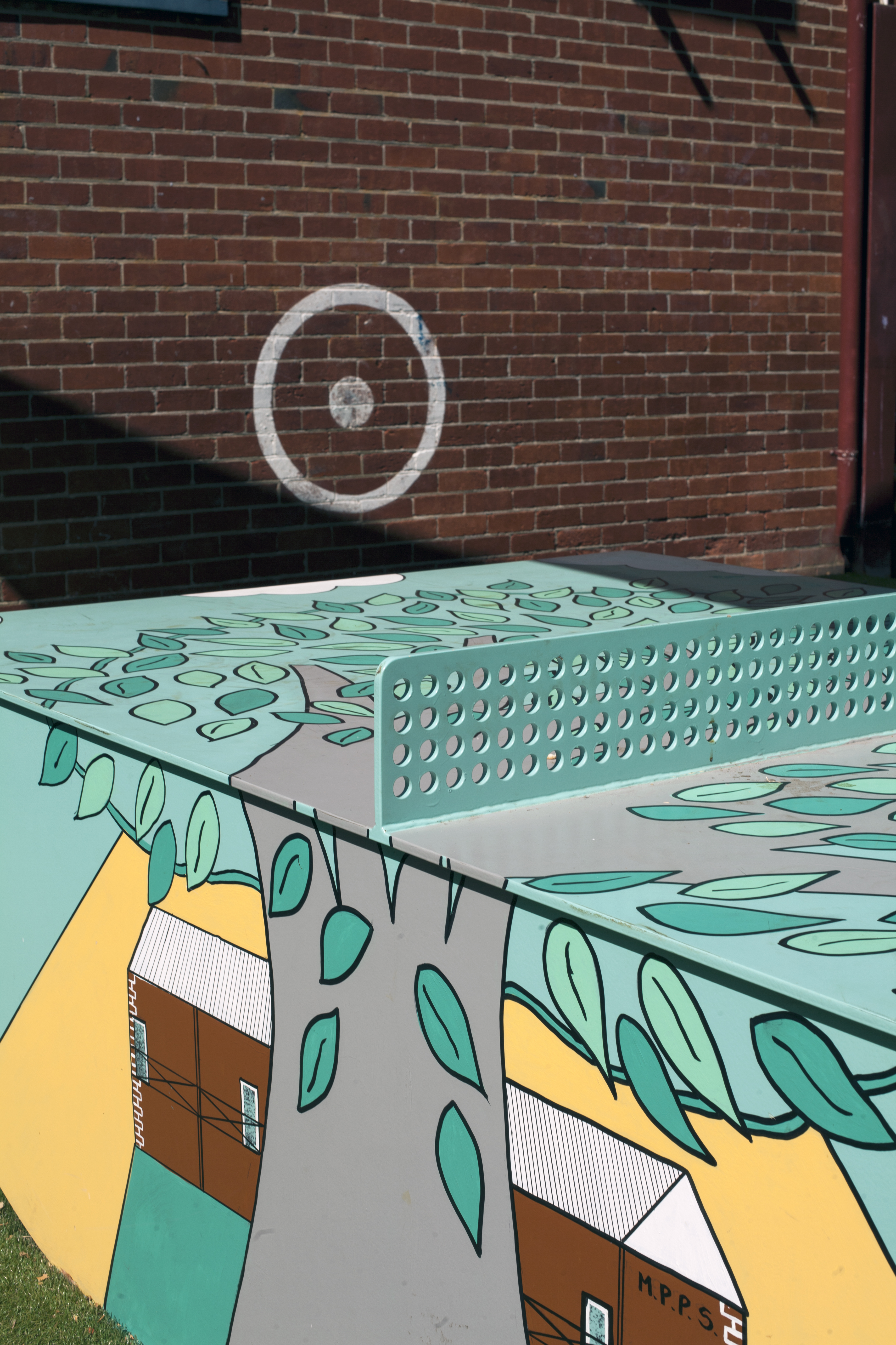 Hand painted outdoor table tennis table. adorned with students art work including trees, waves, ice creams, books, hats, surfboards.