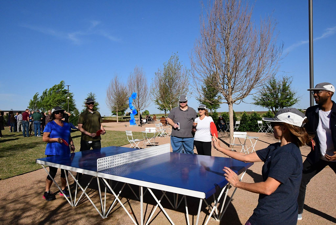 A group stands around and watches a game of outdoor ping pong on the POPP ICON table in blue and white in the Peña Park at the heart of Cypress Waters in Dallas Texas