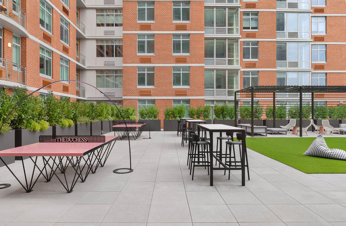two pink outdoor table tennis tables sit alongside cabanas and outdoor tables at the duchess multi-family development in New Jersey
