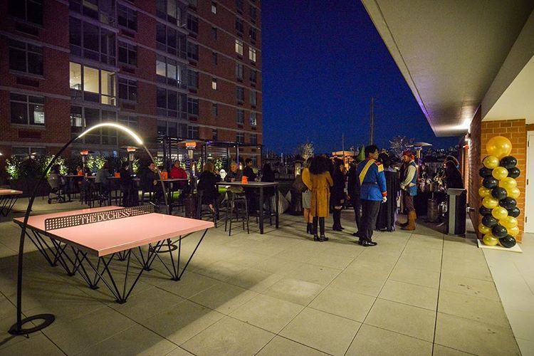 at an opening party two lit up pink outdoor table tennis tables sit alongside cabanas and outdoor tables at the duchess multi-family development on the Hudson river in New Jersey
